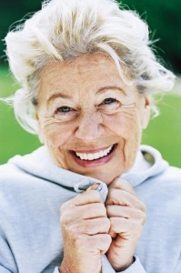 Mature woman clasping sweatshirt under chin, smiling, portrait